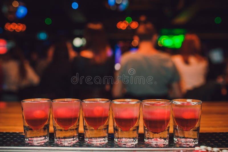 Bartendern häller tequila in i exponeringsglas mot bakgrunden av stången fotografering för bildbyråer