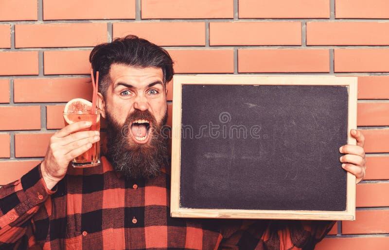 Bartendern hipster rymmer coctailen och advertizing Mannen rymmer exponeringsglas fotografering för bildbyråer