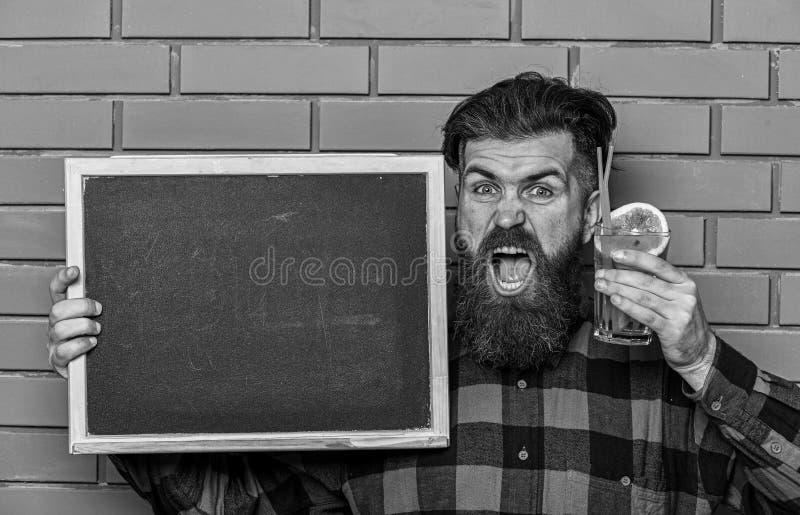 Bartendern hipster rymmer coctailen och advertizing Mannen rymmer exponeringsglas arkivfoto