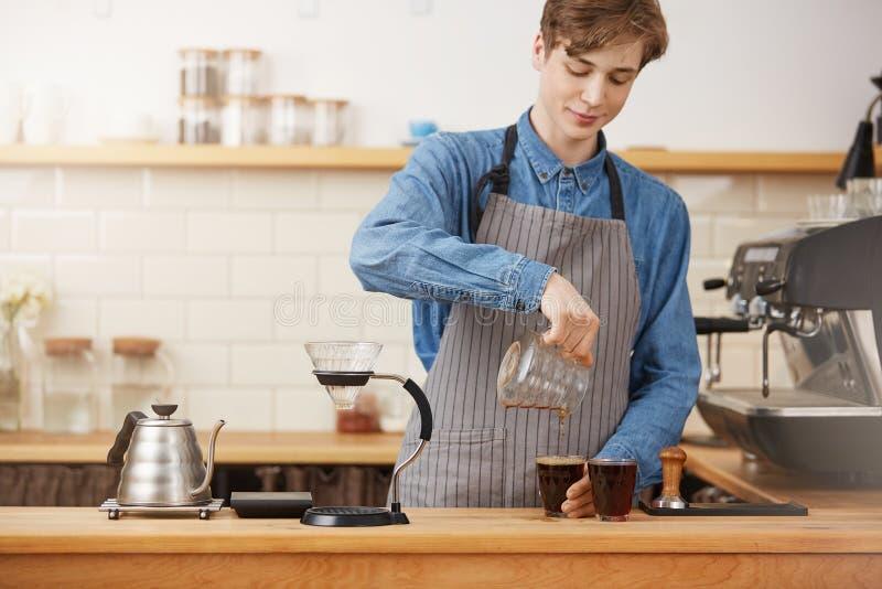 Bartendern räcker hällande alternativt kaffe in i två glass koppar royaltyfri fotografi