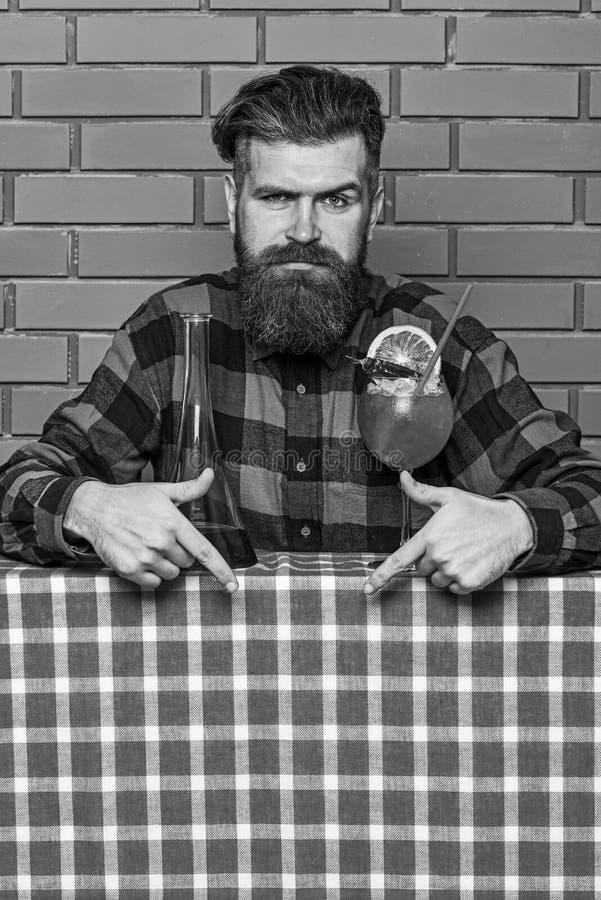Bartendern rekommenderar att försöka drycken Bartender med skägget på strikt framsida som ner pekar med pekfingret Man i rutigt royaltyfri fotografi