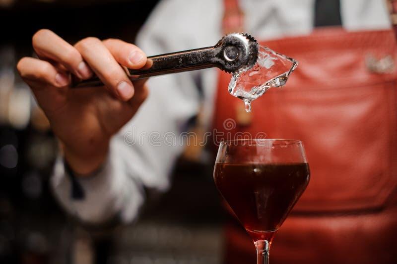 Bartendern sätter en is in i coctailen arkivbilder