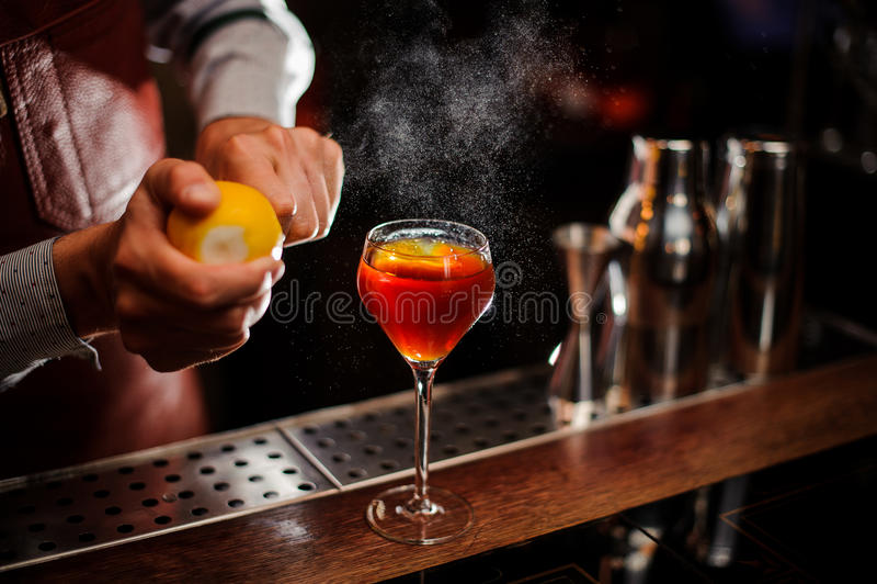 Bartendern tillfogar citronpiff till coctailen på stångräknaren Selektivt fokusera arkivbilder