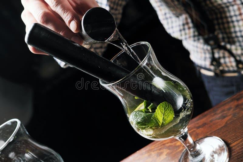Bartendern tillfogar mintkaramellen till coctailen på stångräknaren royaltyfri fotografi