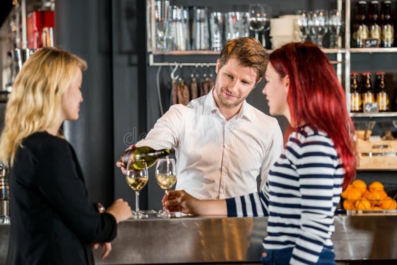 BartenderServing Wine To kunder i stång royaltyfria bilder