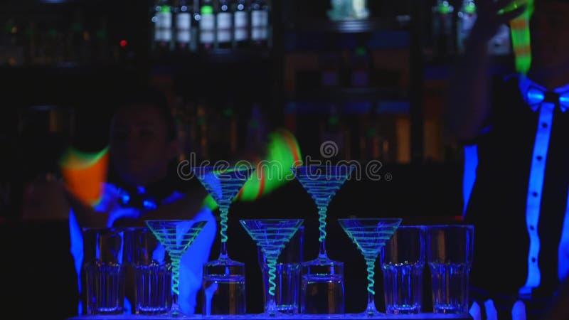 Bartendershow Två bartendrar jonglerar flaskor och dryckeskärlen för blandning close upp arkivfoton