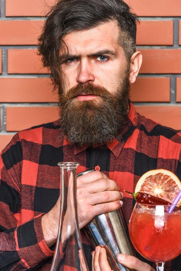 Bartending pojęcie Barman z długą brodą, wąsy i elegancki włosy na surowym twarzy mienia potrząsaczu, robić alkoholiczka zdjęcie royalty free