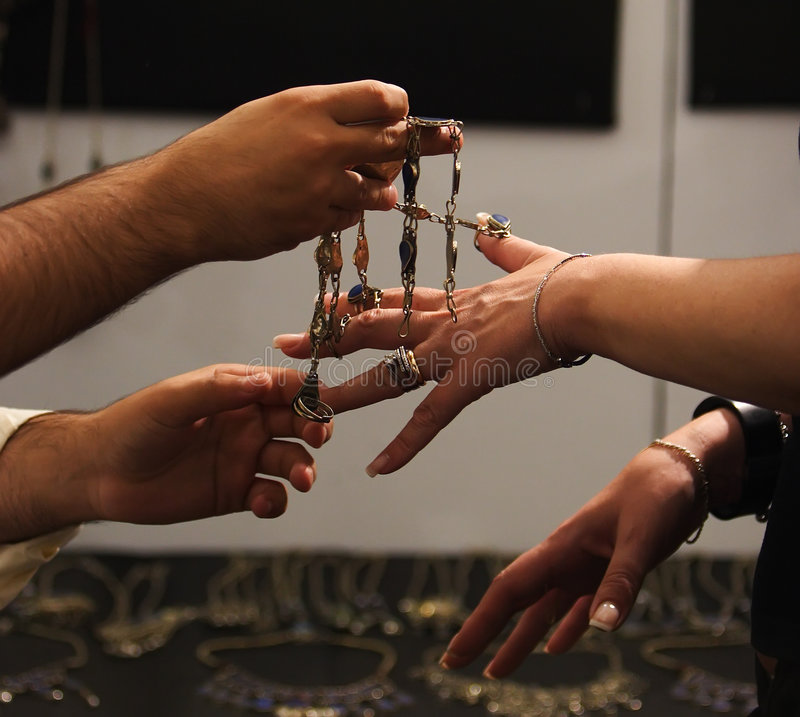 Bartering. Hands trading jewelry during a fair royalty free stock photo