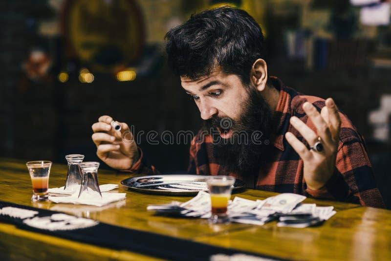 Bartrinken entsetzter Mann bei Tisch mit Alkohol trinkt, Geld stockfotografie