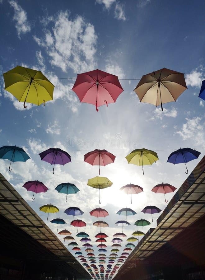 Barwiący parasolowy obwieszenie nad dachem przez cały ulicy na pięknym błękitnym dniu obrazy stock