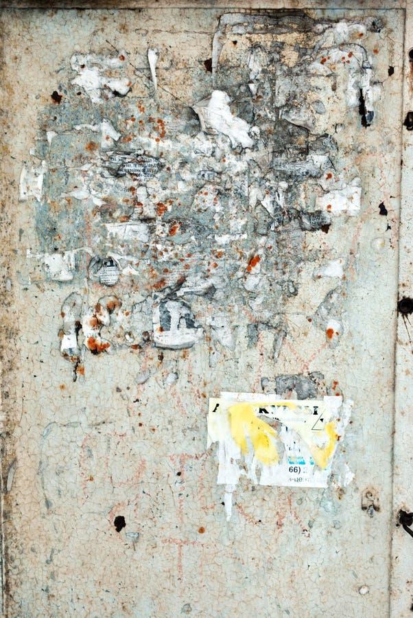 Barwiący tynk na ścianie z poszarpanymi świstkami stare papierowe reklamy w których tylko przerzedże listy rozpoznawalny zdjęcie royalty free
