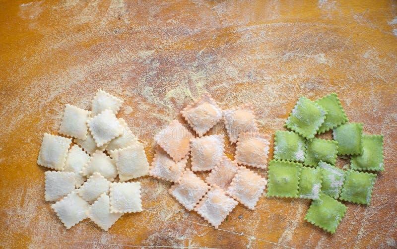 Barwiący uncooked pierożek na tnącej desce, rozpryskanej z mąką zdjęcia royalty free