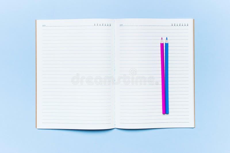 Barwi ołówki i czystego notatnika w linii na błękitnego tło odgórnego widoku mieszkania kopii nieatutowej przestrzeni Drewniani b fotografia stock