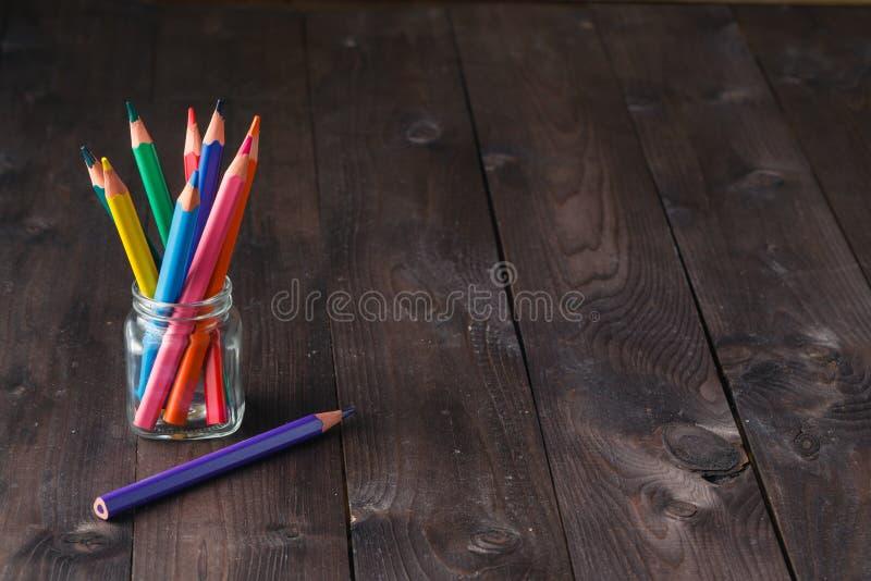 Barwi ołówki w statywowym właścicielu na drewnianym rocznika tle obraz royalty free