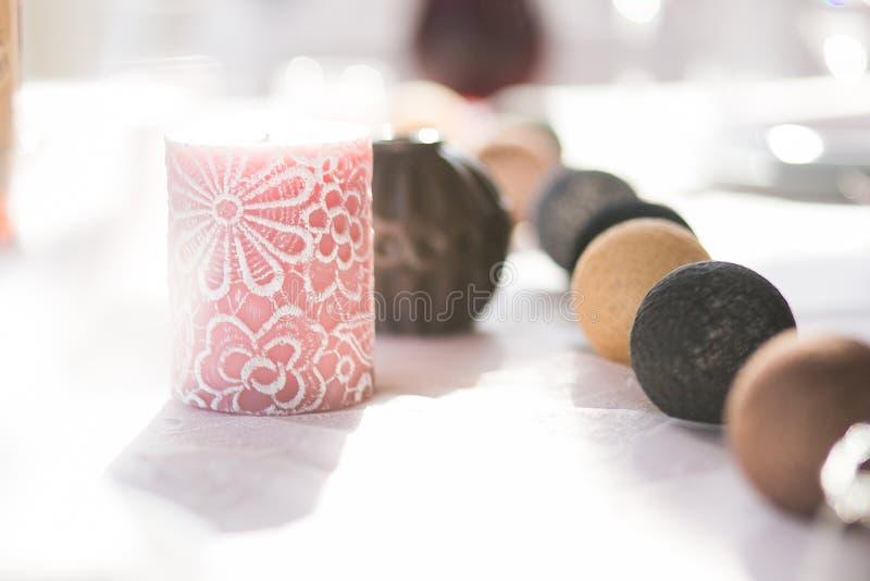 Barwiona Bawełnianej piłki girlanda i świeczka na stole w słońcu zaświecamy Miękcy pastelowi kolory Bożenarodzeniowa nowego roku  obrazy stock