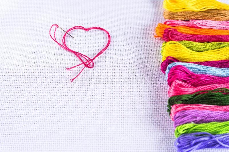 Barwiona nić dla broderii na białej kanwie, igła z czerwoną nicią w formie serca Pojęcie miłość dla hobby obrazy royalty free