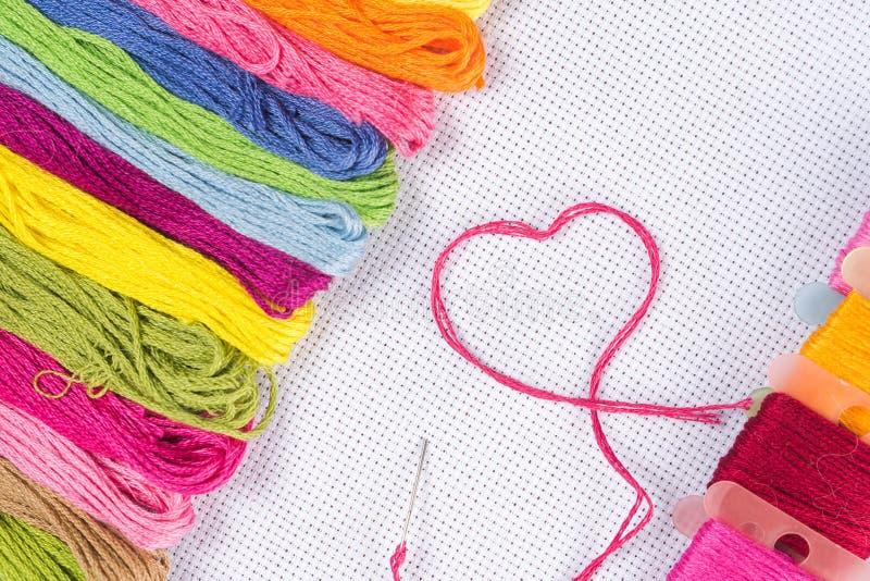 Barwiona nić dla broderii na białej kanwie Pojęcie miłość dla hobby zdjęcie royalty free