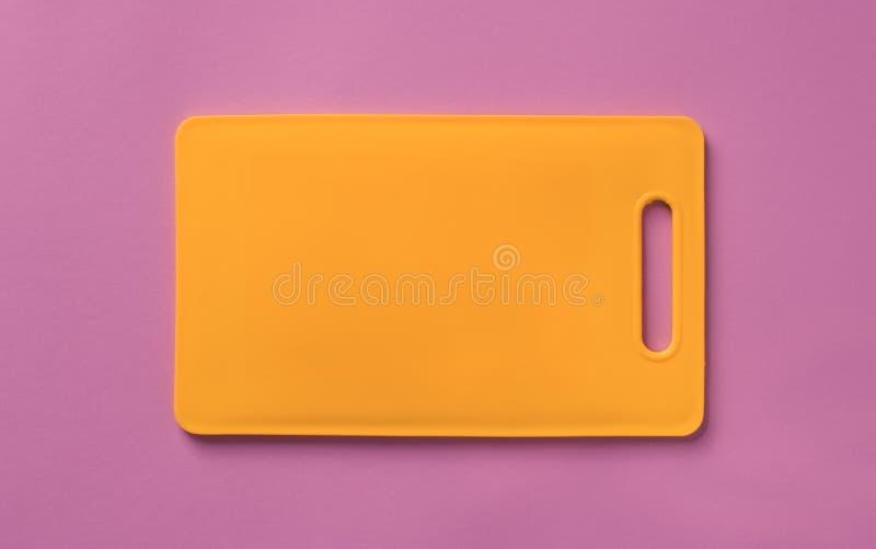 Barwiona pomarańczowa plastikowa tnąca deska na purpurowym tle zdjęcie royalty free