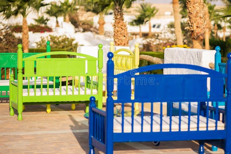 Barwione ławki na tle drzewka palmowe w jaskrawym słonecznym dniu zdjęcia royalty free