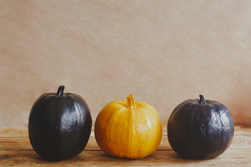 Barwione Halloween banie na drewnianym biurku differenced Samotnie wśród inny Pojedyncza pomarańczowa bania czarne banie z rzędu zdjęcia royalty free
