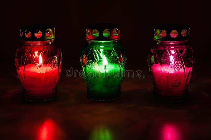 Barwione płonące wotywne świeczki w zmroku obrazy stock