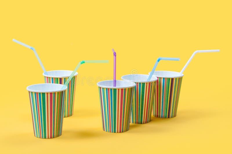 Barwione papierowe filiżanki i tubki na żółtym tle obrazy stock