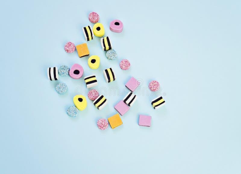 Barwioni żuć cukierki na błękitnym tle zdjęcie stock
