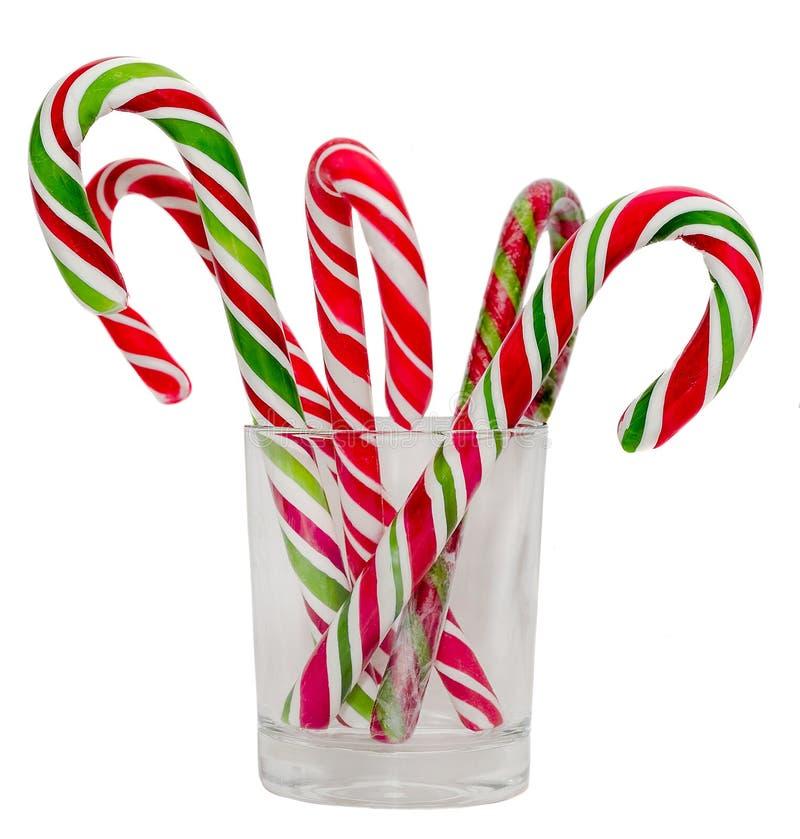 Barwioni cukierków kije i Bożenarodzeniowi lizaki w przejrzystym szkle, odizolowywający, biały tło, zdjęcie stock