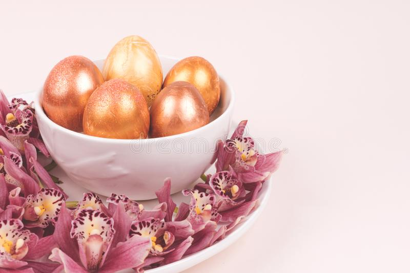 Barwioni jajka na talerzu z storczykowym okwitnięciem fotografia stock