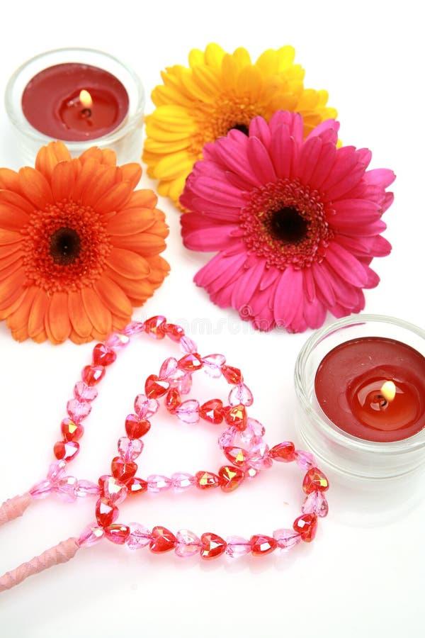 Barwioni kwiaty, płonące świeczki i dwa serca, obrazy stock