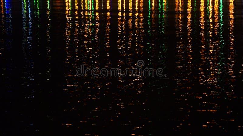 Barwioni nocy miasta światła na wody powierzchni zdjęcia royalty free