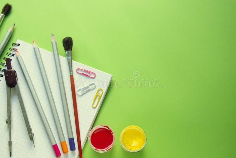 Barwioni ołówki, farby, kompasy, papierowe klamerki i muśnięcia na notatniku, zielony tło z kopii przestrzenią zdjęcie stock