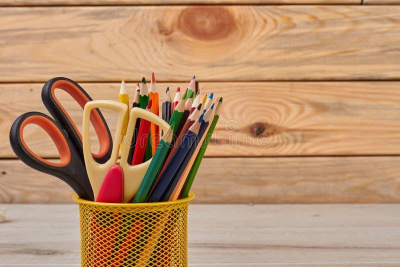 Barwioni ołówki i nożyce w koszu zdjęcie royalty free