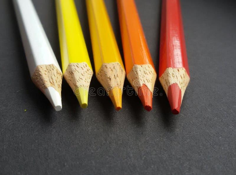 Barwioni ołówki nad czarnym tłem kolory grżą Biel, kolor żółty, pomarańcze i czerwień, obrazy stock