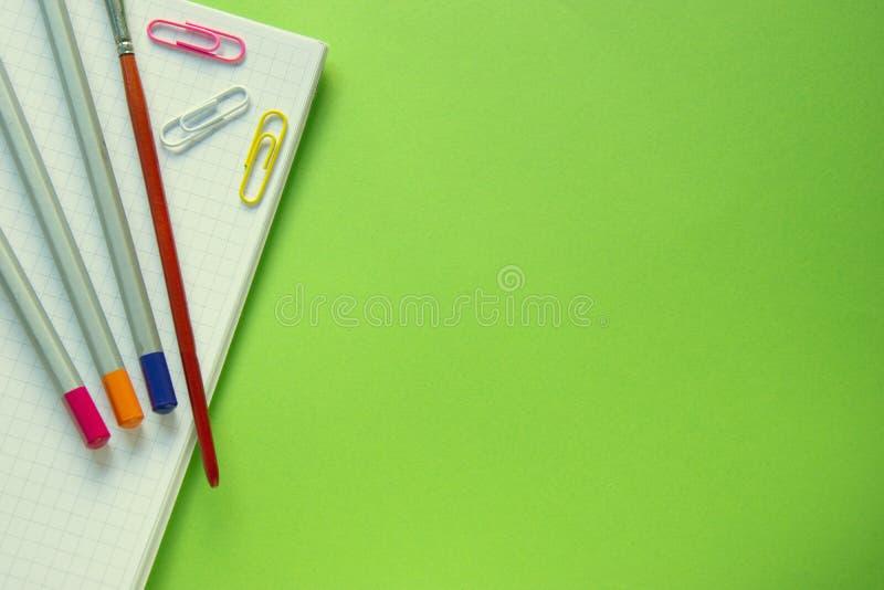 Barwioni ołówki, papierowe klamerki i muśnięcie na notatniku, zielony tło z kopii przestrzenią obrazy stock