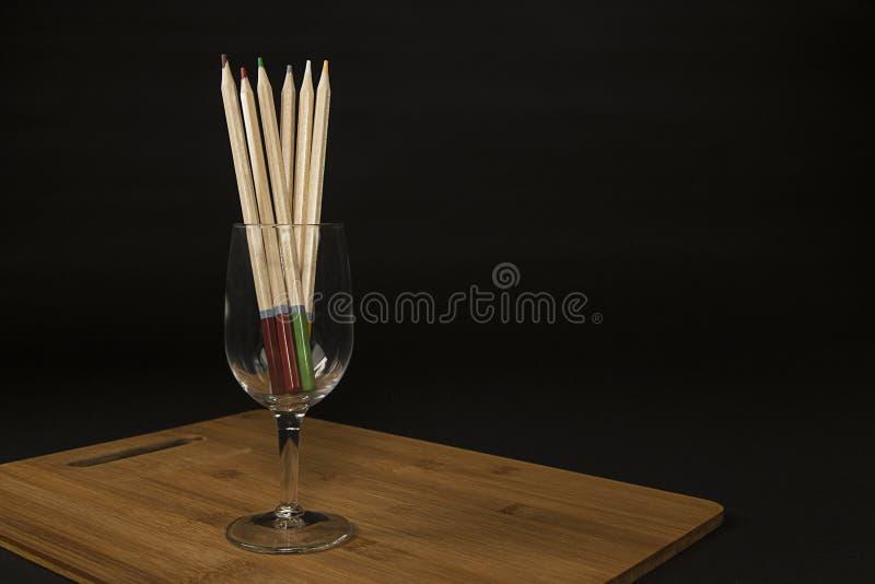 Barwioni ołówki w wina szkle na tnącej desce obraz stock