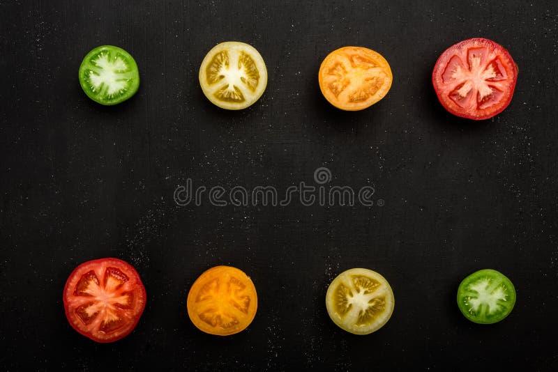 Barwioni pomidory ciący w połówce przy dnem rama i wierzchołkiem Świezi warzywa, kopii przestrzeń obrazy royalty free