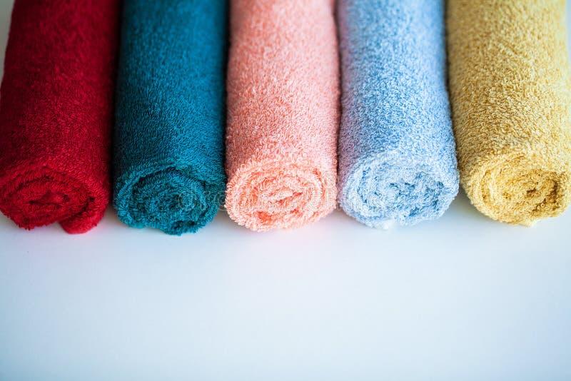 Barwioni ręczniki na bielu stole z kopii przestrzenią na kąpielowym izbowym tle obrazy royalty free