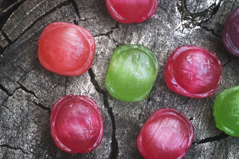 Barwioni słodcy lizaki kłama na fiszorek drewnianej teksturze osrebrzają obrazy stock