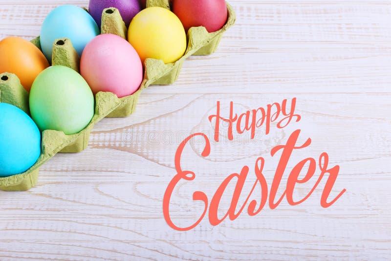 Barwioni Wielkanocni jajka w niecce na białym drewnianym stole, Tekst, szczęśliwy Easter fotografia stock