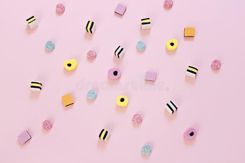 Barwiony cukierek rozpraszający na różowym tle obrazy royalty free
