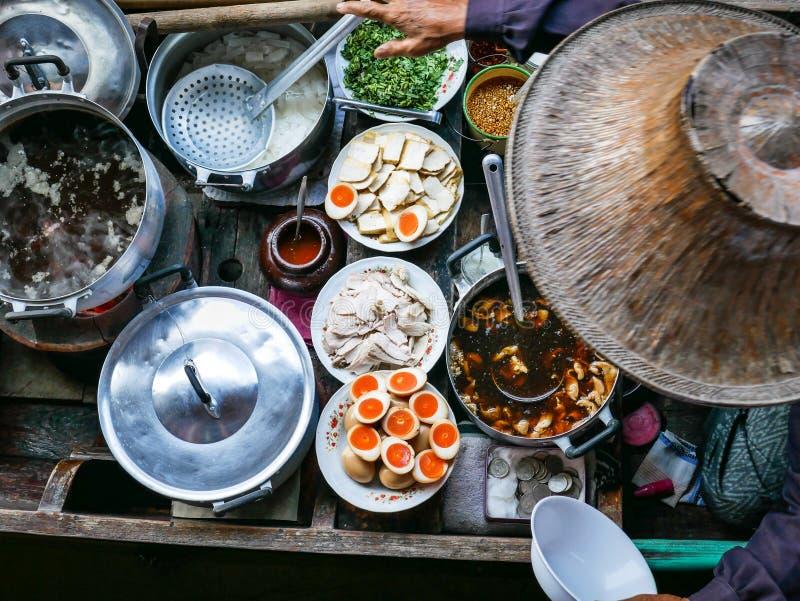 Barwiony tajlandzki jedzenie w spławowym rynku, karmowy sprzedawca z tradycyjnym kapeluszem w Tajlandia zdjęcia stock