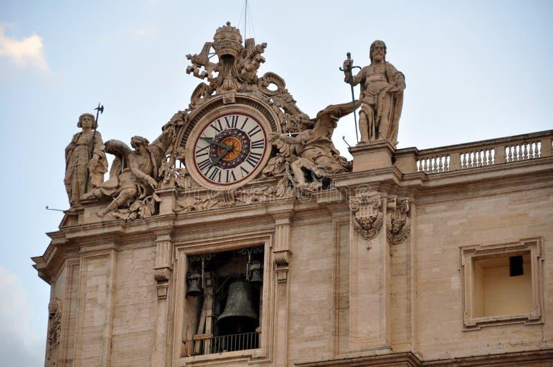 Basílica de San Pedro en la Ciudad del Vaticano La opinión de ángulo izquierda adornó por algunas estatuas de santos y de un relo fotos de archivo