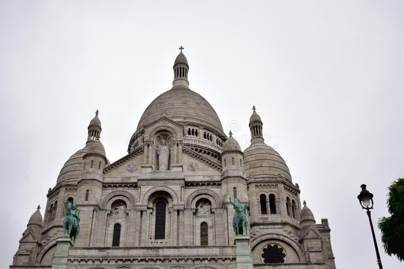 Basílica del corazón sagrado Sacre Coeur París, Francia, fachada con las estatuas, la bóveda y las torres Día lluvioso, cielo gri imagen de archivo libre de regalías