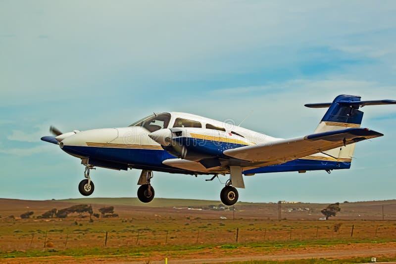 Bas avion jumel volant de bleu et blanc de moteur images stock