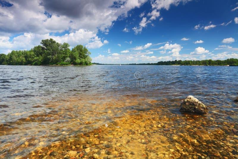 Bas de fleuve avec des pierres dans l'eau transparente image stock