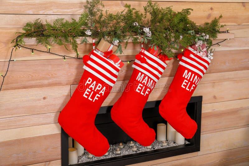 Bas de Noël accrochant sur le mur en bois près de la cheminée décorative image libre de droits