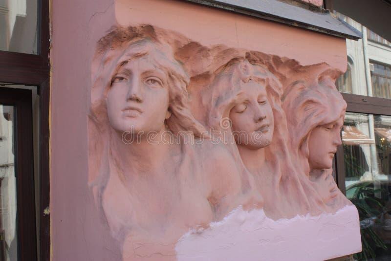 bas-hulp van de hoofden van vrouwen op de voorgevel van het gebouw in Petersburg stock fotografie
