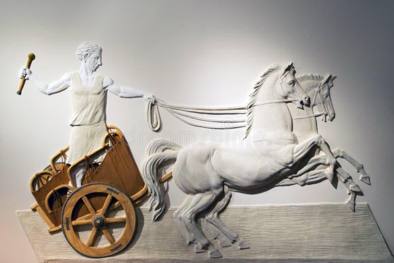 Bas-hulp van Roman Centurion die een blokkenwagen drijven stock afbeeldingen