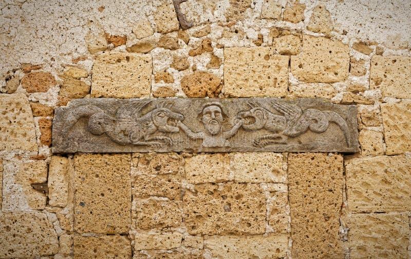 Bas-relevo antigo em uma parede do tufo que representa um homem mordido imagens de stock